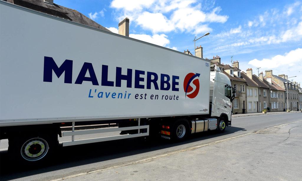 Camion Malherbe roulant dans une petite ville